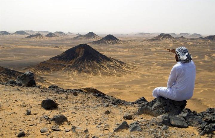 Любуясь вершинами  Мужчина любуется видом вулканических и ветряных пиков Черной пустыни.