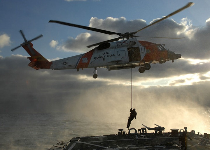 U.S.-Coast-Guardsman-fast-ropes-from-an-HH-60H-Seahawk-helicopter-onto-the-flight-deck-of-the-guided-missile-destroyer-USS-Mitscher