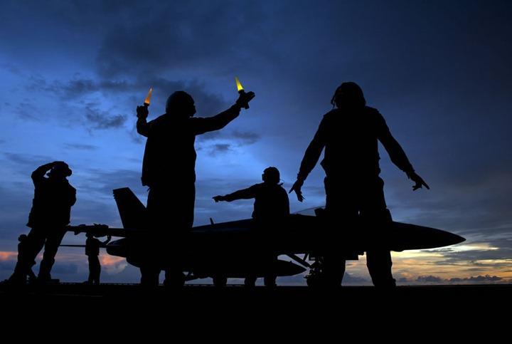 U.S.-Navy-aircraft-director-signals-as-aviation-ordnancemen-unload-ordnance-from-an-Super-Hornet-aircraft-aboard-the-aircraft-carrier-USS-Carl-Vinson