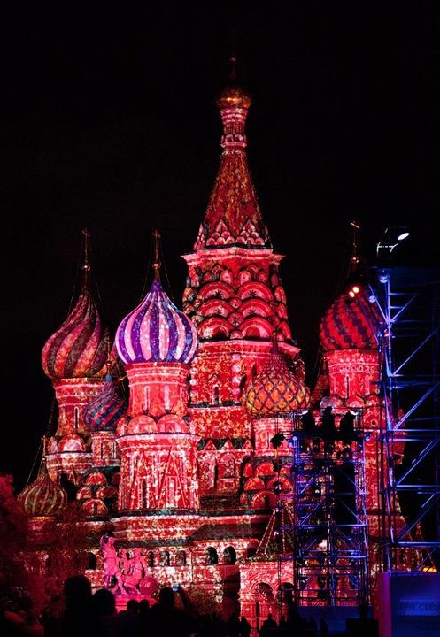 Размах шоу впечатлил: Красная площадь была уставлена вышками, увешанными прожекторами, которые поочередно освещали Кремлевскую стену, Собор Василия Блаженного, здание ГУМа и Исторический музей. Шоу сопровождала не очень мелодичная музыка, но световые узоры с ней так удачно синхронизировались, что громкие звуки не давили на психику. Рулил всем этим оператор в белой будке, куда мне, когда я насмотрелась на узоры, очень захотелось сходить на экскурсию – посмотреть, как это делается и подергать рычажки. На Манежке представление оказалось еще интереснее: если на Красной площади рисунок света был абстрактный, то здесь на здание гостиницы «Москва» и выставочный зал проецировались целые сюжеты. Не буду все это описывать словами – фотографии это сделают гораздо лучше. Хоть многие из них и сняты с одной точки (а иначе никак, ибо не протолкнуться), благодаря потокам света и цвета они на мой взгляд вовсе не кажутся однообразными.