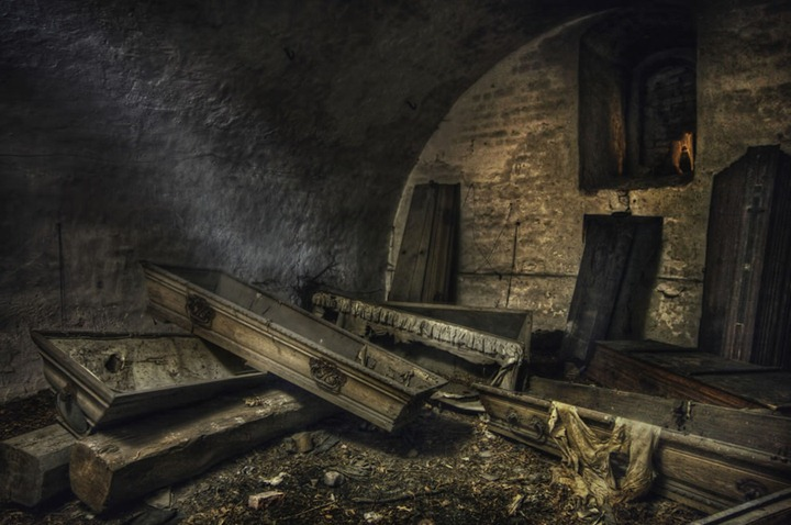 The-black-figure-in-an-old-abandoned-crypt-full-of-mostly-empty-coffins